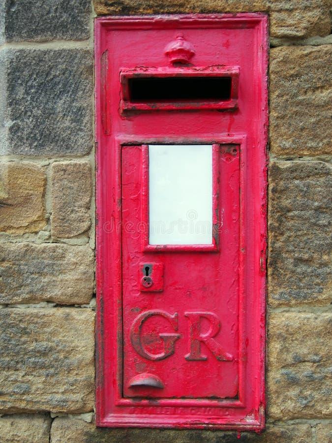 老英国红色岗位箱子在有匙孔的一个石墙设置了 库存照片