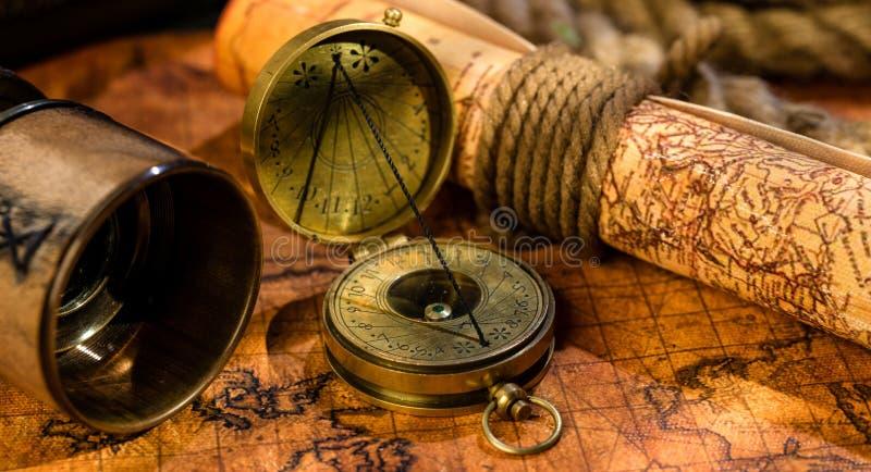 老葡萄酒减速火箭的指南针和小望远镜在古老世界地图 免版税库存图片