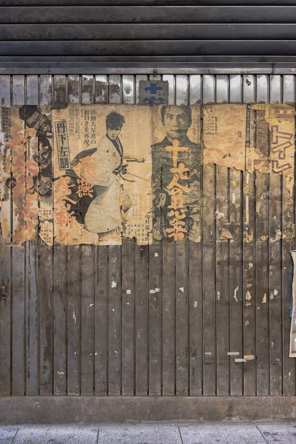 老葡萄酒减速火箭的日本武士电影照片和老缘故品牌的生锈的金属广告标志在地下过道有乐町Concour的 库存图片