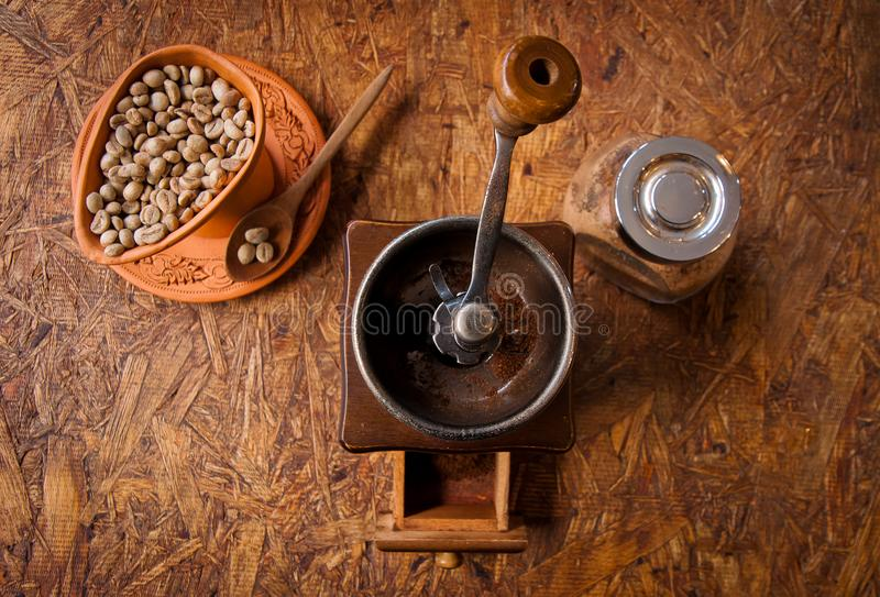 老葡萄酒减速火箭的研磨机和咖啡豆在杯子和匙子顶视图 免版税图库摄影