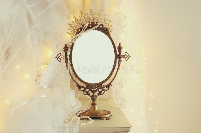 老葡萄酒卵形镜子和美丽的白色婚礼礼服和面纱在椅子与金诗歌选点燃 库存图片