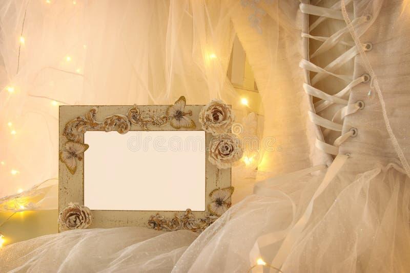 老葡萄酒卵形镜子和美丽的白色婚礼礼服和面纱在椅子与金诗歌选点燃 免版税库存图片