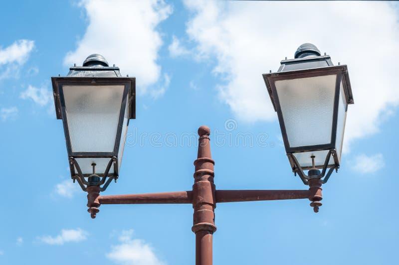 老葡萄酒和生锈的街灯岗位或者灯笼有两个电灯泡的反对美丽的蓝天与白色覆盖背景,关于 免版税库存照片