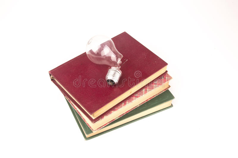 老葡萄酒在白色背景隔绝的书和残破的电灯泡 图库摄影