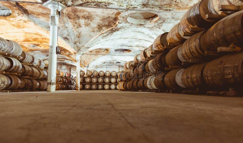 老葡萄酒威士忌酒桶按顺序安置的填装了威士忌酒  免版税库存图片