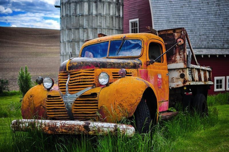 老葡萄酒废弃了在一个红色谷仓前面的卡车 免版税库存图片