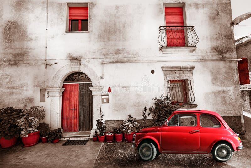 老葡萄酒意大利人场面 小古色古香的红色汽车 老化作用 免版税库存图片