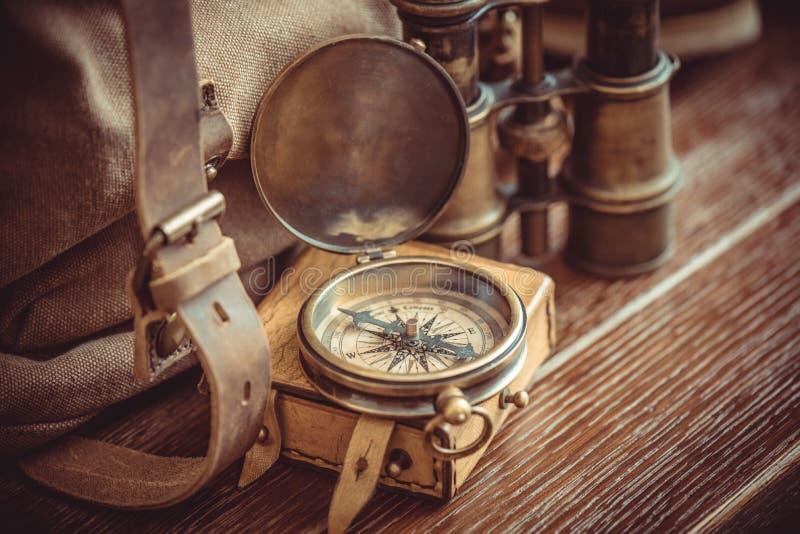 老葡萄酒指南针、双筒望远镜和背包 免版税库存图片