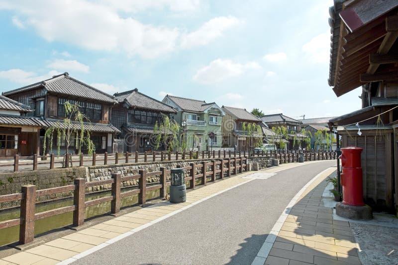 老葡萄酒木日本房子和临近老河 有老镇区域的老砖街道 免版税图库摄影