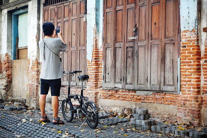 老葡萄酒木门木纹理老砖墙自行车游人骑自行车游览吸引力老房子230岁 Bangk 图库摄影
