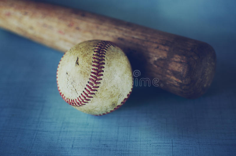 老葡萄酒棒球和棒反对蓝色纹理背景 库存图片