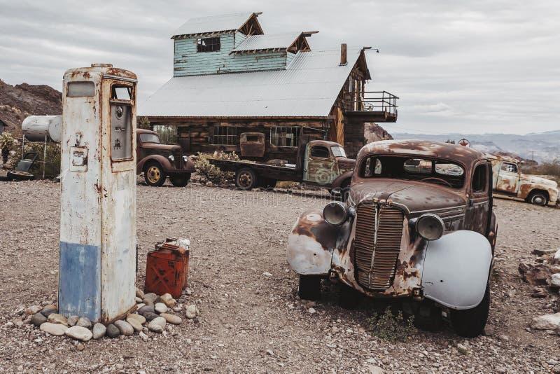 老葡萄酒生锈的汽车卡车在老燃油泵附近放弃了在沙漠 库存图片