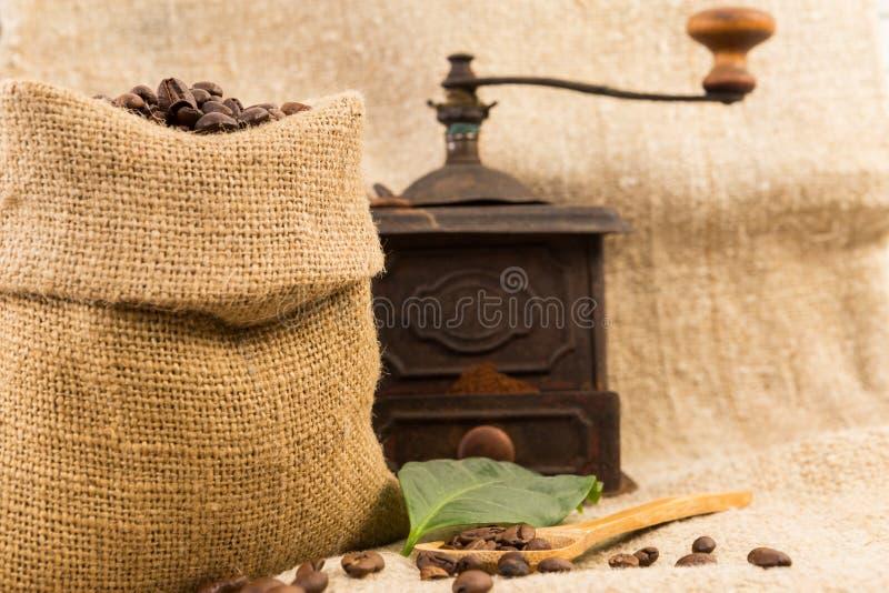 老葡萄酒磨咖啡器和黄麻大袋或者袋子 库存图片