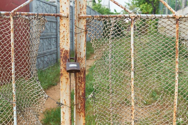 老葡萄酒锁在有褴褛绳索网的生锈的铁门 库存照片