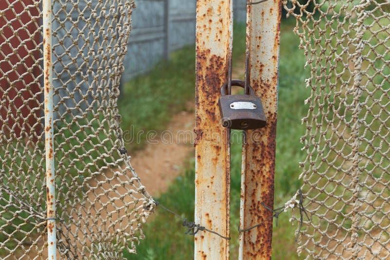老葡萄酒锁在有褴褛绳索网的生锈的铁门 免版税图库摄影