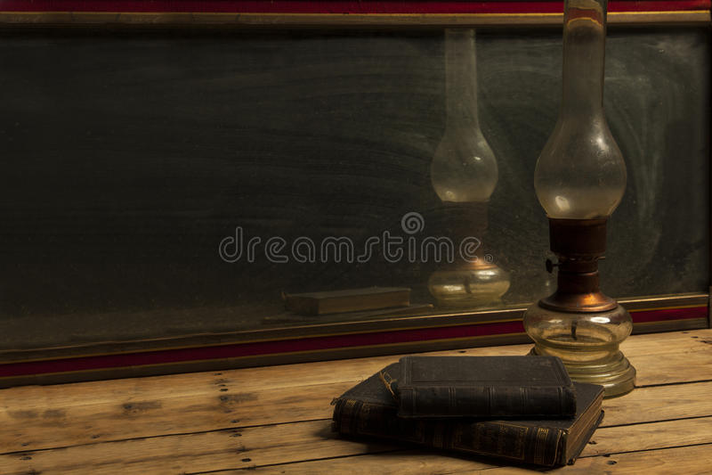 老葡萄酒镜子,有旧书的油灯在木桌 免版税库存图片