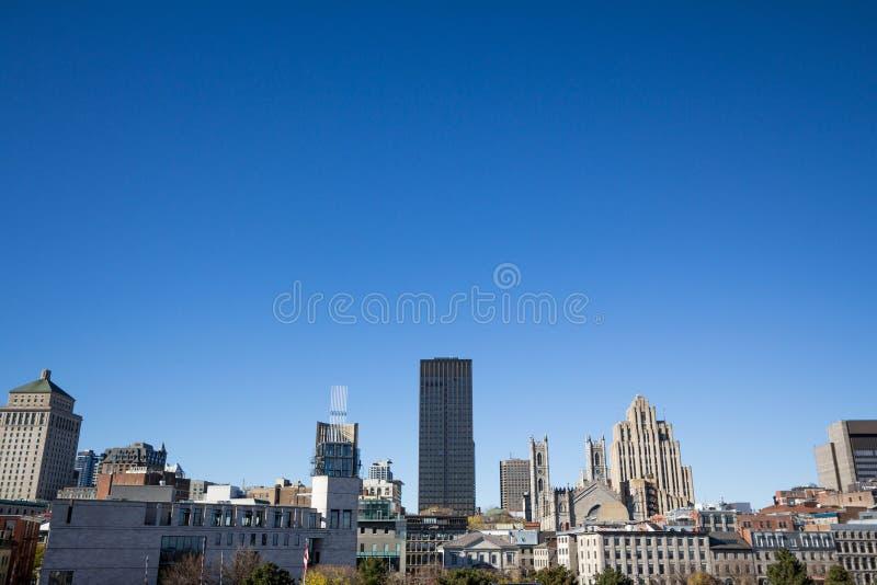 老蒙特利尔的地平线,有在前面的Notre Dame大教堂的和石头和玻璃摩天大楼在背景中 免版税图库摄影