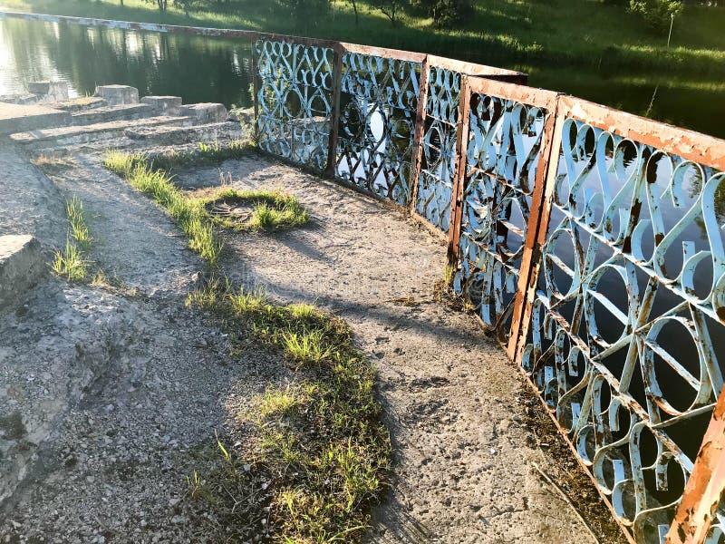 老蓝灰色金属生锈的削皮栏杆,有剥的破裂的油漆篱芭以水,河为背景 库存照片