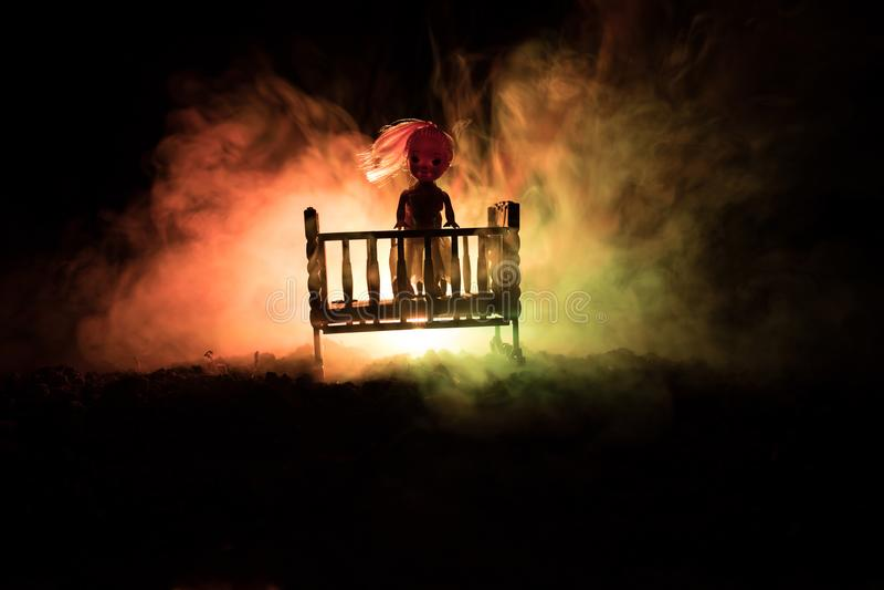 老蠕动的令人毛骨悚然的木婴孩小儿床在黑暗的被定调子的有雾的背景中 恐怖概念 在黑暗的可怕婴孩和床剪影 免版税库存照片
