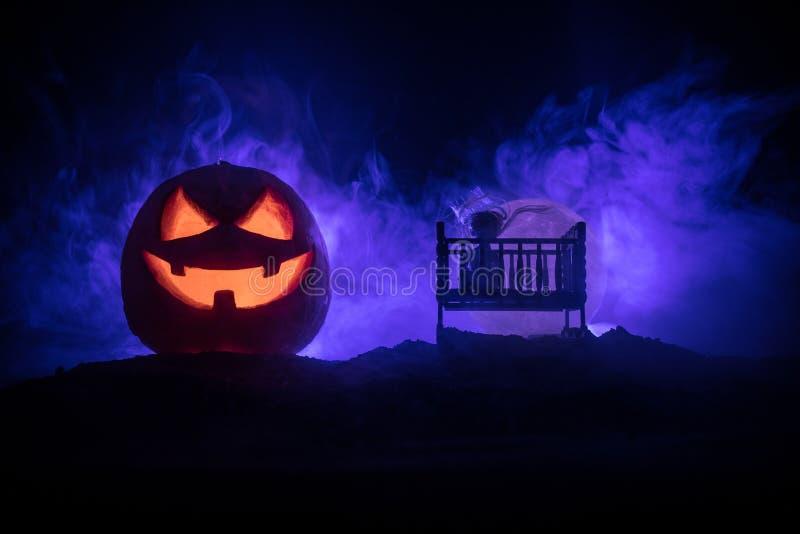 老蠕动的令人毛骨悚然的木婴孩小儿床在黑暗的被定调子的有雾的背景中 恐怖概念 在黑暗的可怕婴孩和床剪影 r 库存照片
