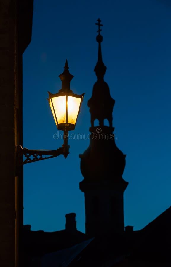 老街灯和教会剪影,塔林 库存照片