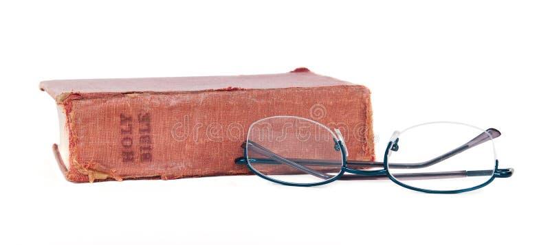 老被佩带的圣经和放大镜 免版税库存图片