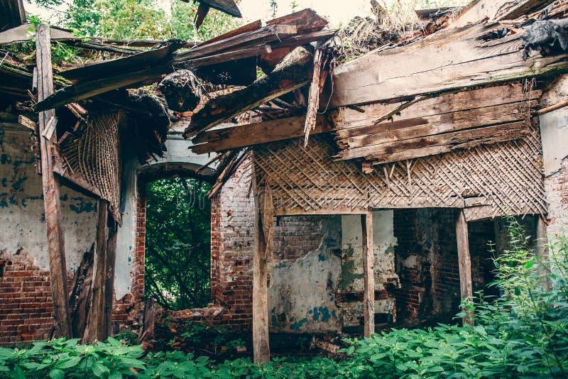 老被放弃的修造的室内部废墟里面与下落的屋顶和长满与草 库存图片