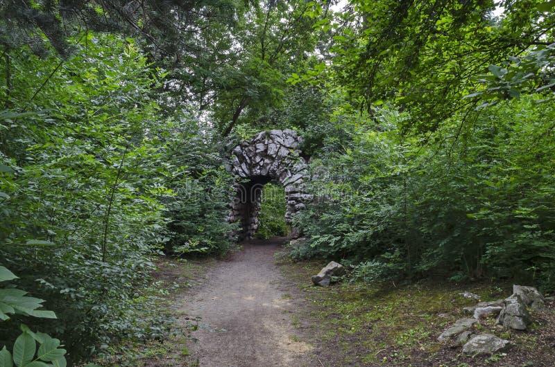 老被放弃的假山庭园看法和石头在自然老西部公园成拱形如毛刷与各种各样的植物 免版税库存图片