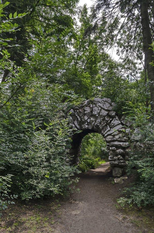 老被放弃的假山庭园看法和石头在自然老西部公园成拱形如毛刷与各种各样的植物 图库摄影