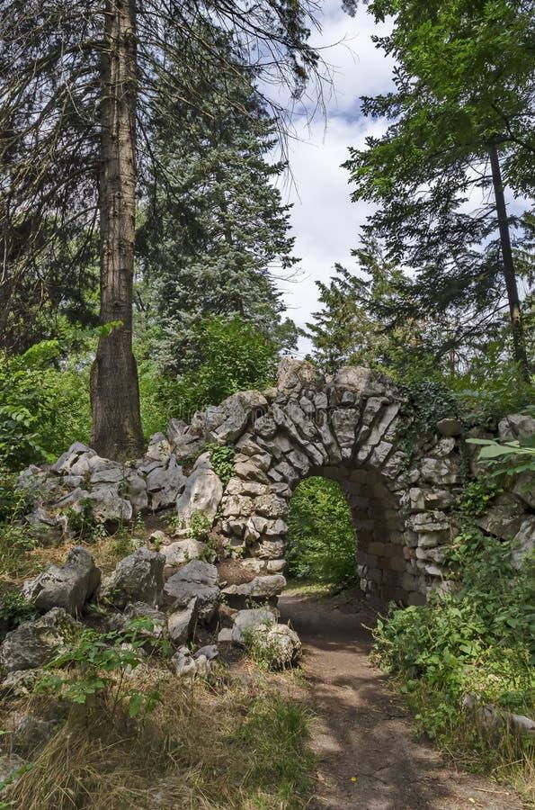 老被放弃的假山庭园看法和石头在自然老西部公园成拱形如毛刷与各种各样的植物 库存图片