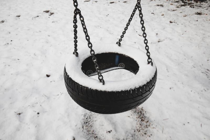 老被放弃的套雪报道的轮胎摇摆反对冬天森林风景背景 童年记忆概念 库存图片