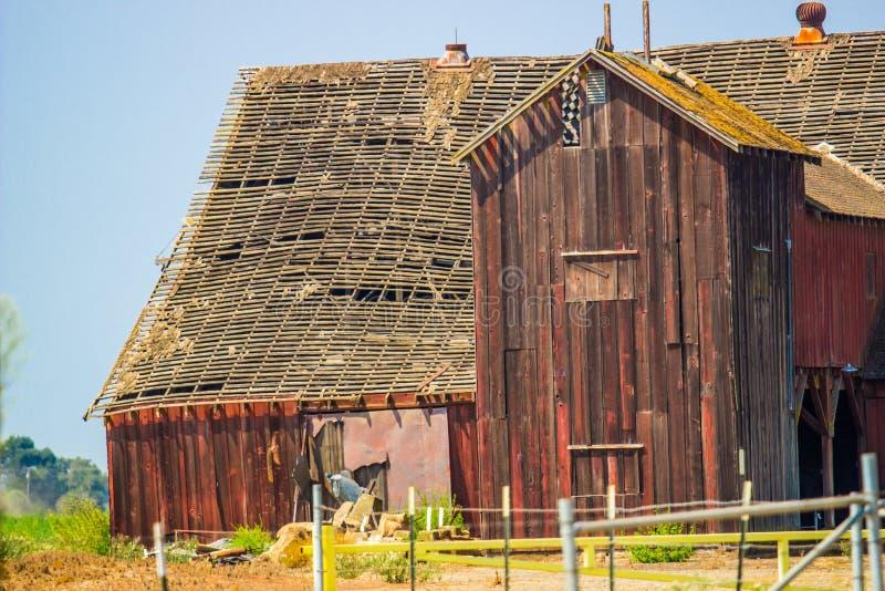 老被放弃的木谷仓与把屋顶进行下去 免版税库存图片