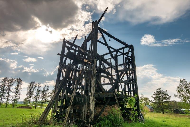 老被烧的风车遗骸在领域的在雨前 免版税库存照片