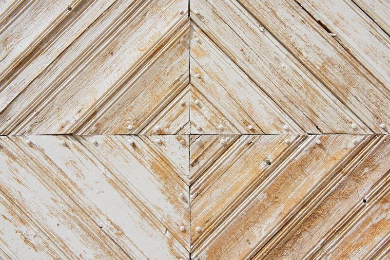 老被风化的白被绘的木门的Rhomb样式 免版税库存照片