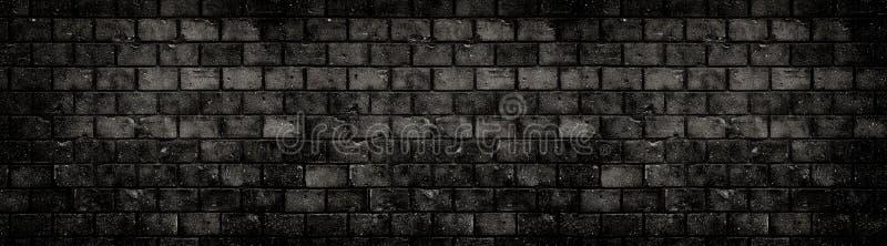 老被风化的脏的黑黑暗的具体块砖墙纹理背景被放弃的房子孔镇压宽横幅背景 免版税图库摄影