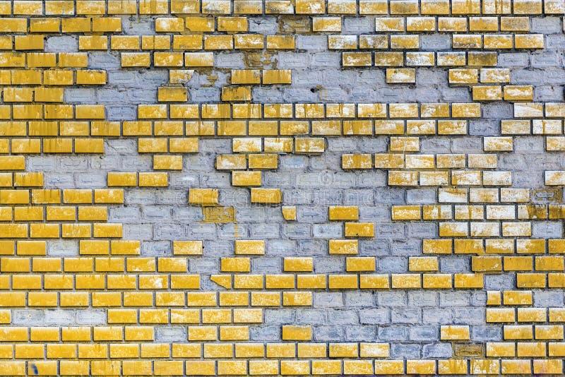 老被风化的黄色绘了有元素丢失的砖墙 与零件的年迈的块表面掉下 具体难看的东西 免版税库存图片