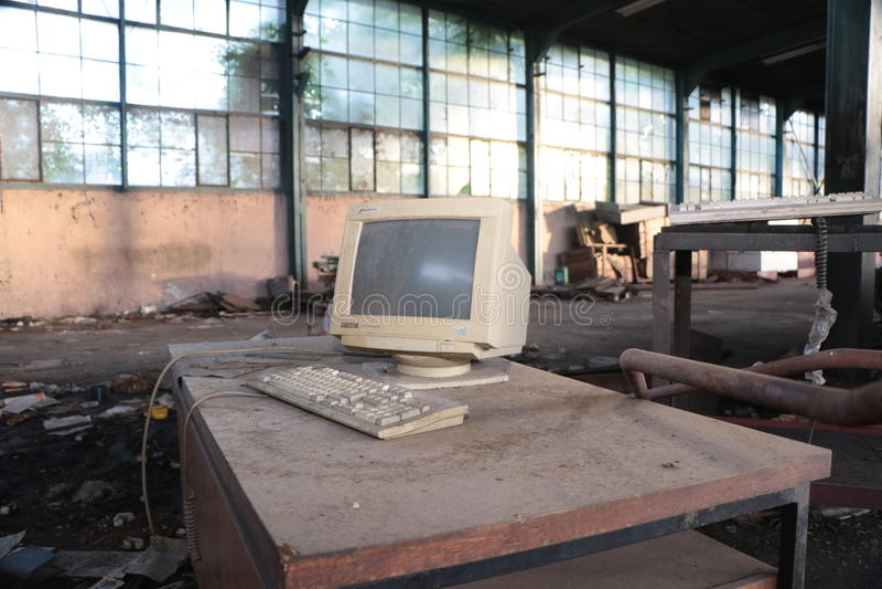 老计算机在被破坏的工厂 库存照片
