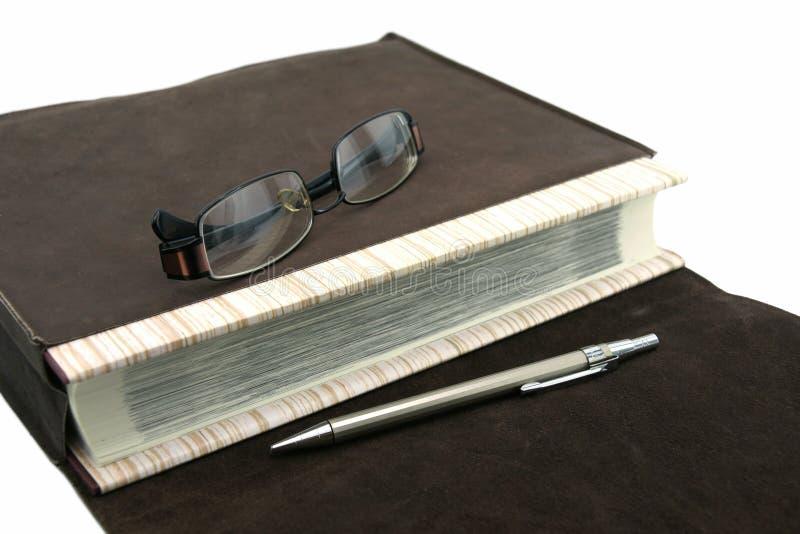 老课本或圣经与笔和镜片和皮包 图库摄影