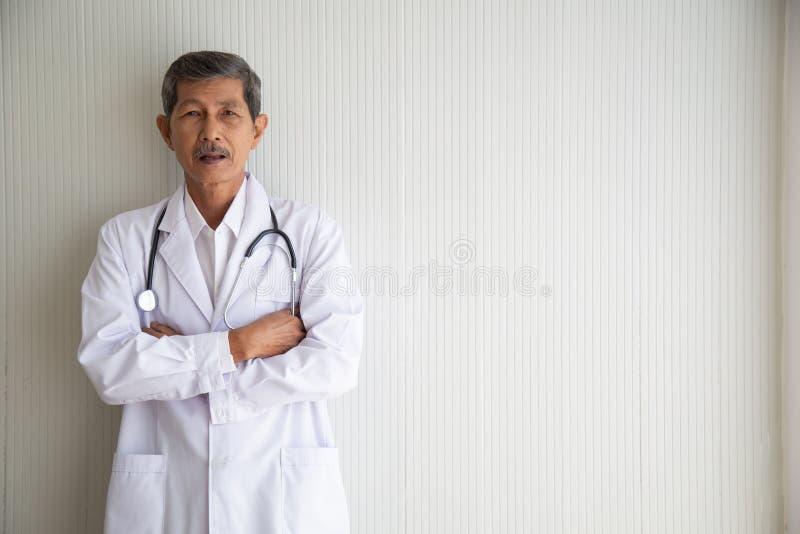 老资深亚洲医生微笑画象与制服的 免版税库存图片