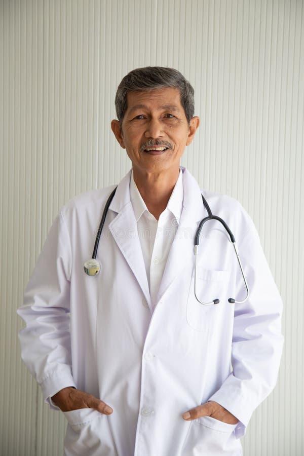 老资深亚洲医生微笑画象与制服的 免版税库存照片