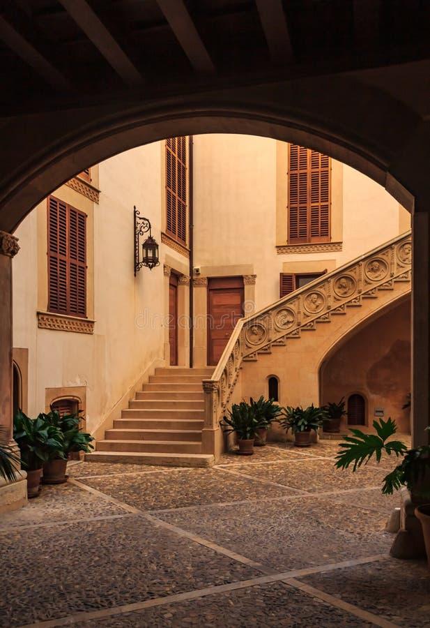 老赤土陶器在住宅邻里在帕尔马上色了有进行下去一个黑暗的拱道的一个大楼梯的庭院 图库摄影
