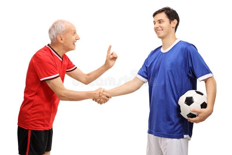 老足球运动员与年轻球员握手 免版税库存照片