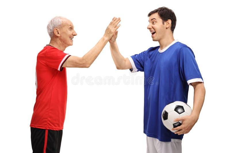老足球运动员和一年轻足球运动员高fiving 免版税库存照片