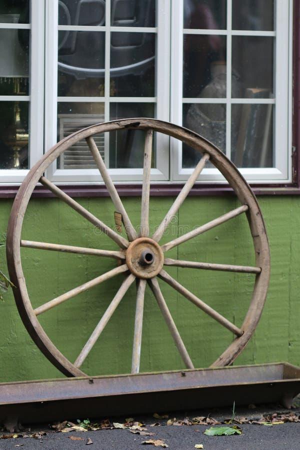 老轮子是在窗口前面 免版税库存照片