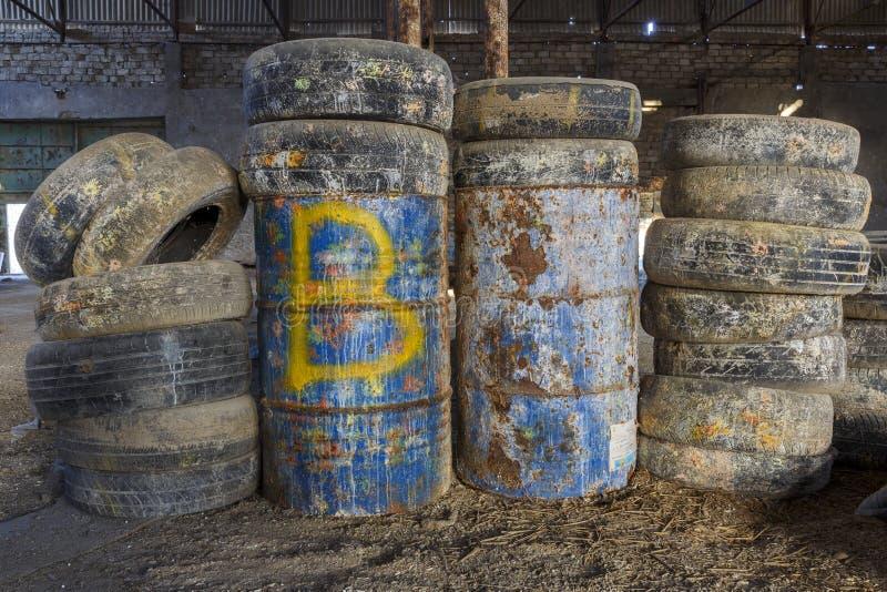 老轮胎和桶在一个被放弃的飞机棚 库存照片