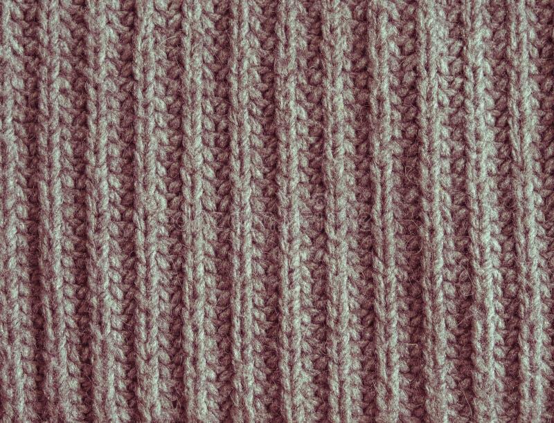 老退色红色或被编织的桃红色羊毛构造抽象背景 库存照片