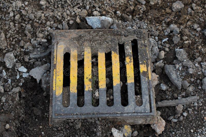 老金属街道人孔盖绘与黄色油漆 路重建 下水道舱口盖 免版税库存图片