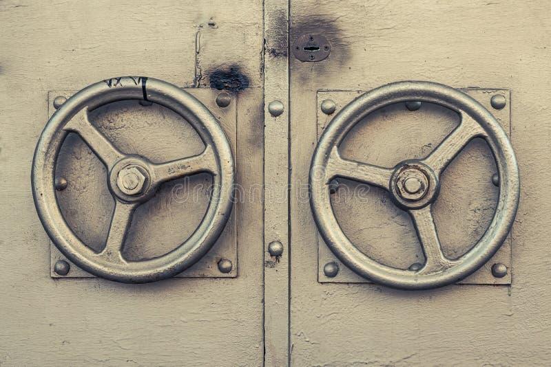 老金黄门把手 以金色方向盘的形式金属玉米色门把手 两金属金门把手 免版税库存照片