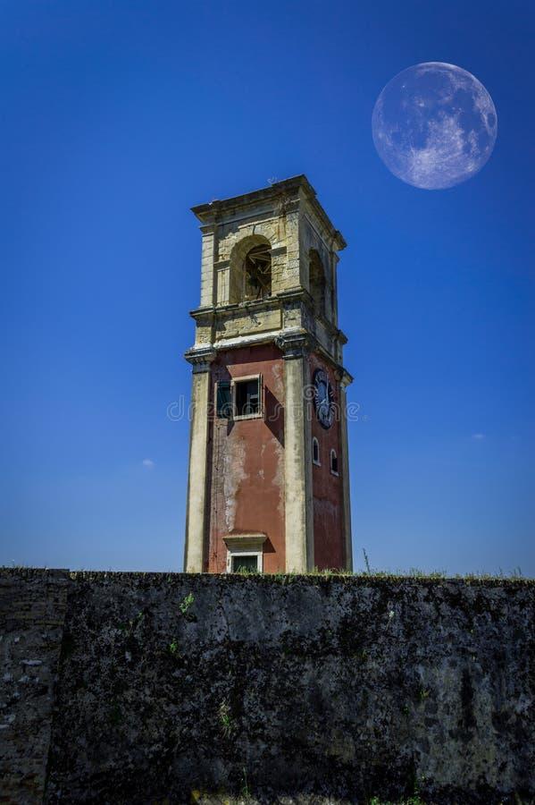 老钟楼和月亮在它后在老堡垒在科孚岛镇希腊 免版税库存照片