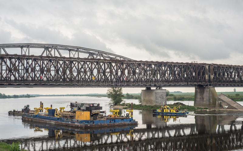 老钢桥梁间距的片段在一座新的桥梁的工地工作的 免版税库存图片